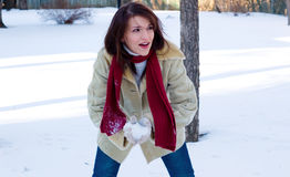 Snowball fight time. A playful young woman in a snowball fight stock photo