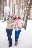 Snowball fight. Winter couple having fun playing in snow outdoor. S. Young joyful couple in love stock photo