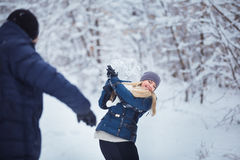 Snowball fight. Winter couple having fun playing in snow outdoors. Young joyful couple. Royalty Free Stock Images