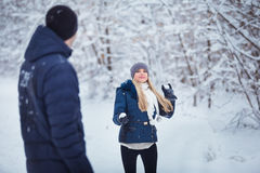 Snowball fight. Winter couple having fun playing in snow outdoors. Young joyful couple.
