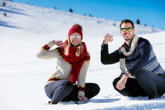 Snowball fight. Winter couple having fun playing in snow outdoors. Young joyful happy multi-racial couple. Snowball fight. Winter couple having fun playing in Royalty Free Stock Photos