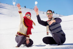 Snowball fight. Winter couple having fun playing in snow outdoors. Young joyful happy multi-racial couple. Stock Photo
