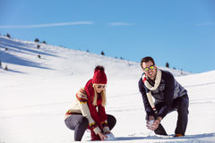 Snowball fight. Winter couple having fun playing in snow outdoors. Young joyful happy multi-racial couple. Royalty Free Stock Images