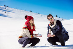 Snowball fight. Winter couple having fun playing in snow outdoors. Young joyful happy multi-racial couple. Royalty Free Stock Photography