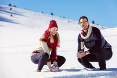 Snowball fight. Winter couple having fun playing in snow outdoors. Young joyful happy multi-racial couple. Stock Photos