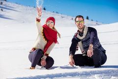 Snowball fight. Winter couple having fun playing in snow outdoors. Young joyful happy multi-racial couple. Snowball fight. Winter couple having fun playing in Royalty Free Stock Photo