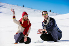 Snowball fight. Winter couple having fun playing in snow outdoors. Young joyful happy multi-racial couple. Stock Images