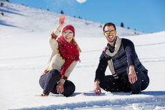 Snowball fight. Winter couple having fun playing in snow outdoors. Young joyful happy multi-racial couple. Stock Image