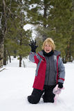 Snowball fun. Active retired woman playing in the snow and throwing snowballs Stock Photo