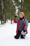 Snowball fun. Active retired woman playing in the snow and throwing snowballs Stock Photos