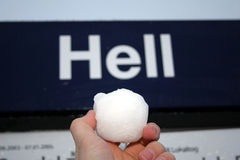Snowball in Hell. A hand holding a snowball infront of the sign Hell Royalty Free Stock Image