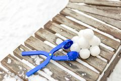 Snowball maker tool with set of ready snowballs . Blue plastic snowball maker tool with set of ready snowballs laying on a wooden bench near outdoor children Stock Images
