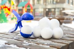 Snowball maker tool with set of ready snowballs . Blue plastic snowball maker tool with set of ready snowballs laying on a wooden bench near outdoor children Royalty Free Stock Images