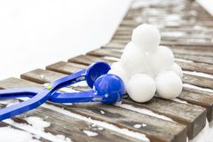 Snowball maker tool with set of ready snowballs . Blue plastic snowball maker tool with set of ready snowballs laying on a wooden bench near outdoor children Royalty Free Stock Photo