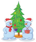 Snowballs and Christmas tree. Cartoon, snowmans with holiday gifts under the Christmas tree Royalty Free Stock Photo