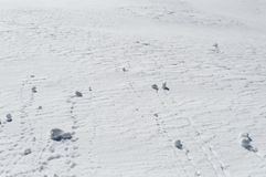 Snowballs rolling down a snowy slope on top of the mountain royalty free stock photo