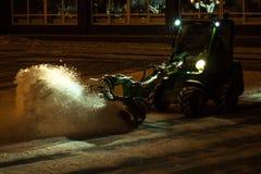 Snowblower извлекает снег в вечере стоковые изображения rf