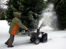 Snowblower. Man in parka clearing a path with a snowblower after a snowstorm Stock Image