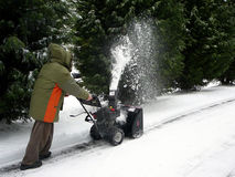 Snowblower. Man in parka clearing a path with a snowblower after a snowstorm Stock Photos
