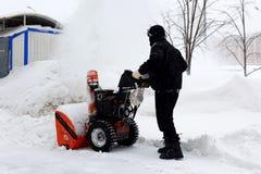 Snowblower in city. Under snowfall Stock Image