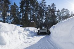 Snowblower at work on a winter day. Snowplow removing snow after blizzard. Clearing the ice. Snow removal machine. Clear driveway. With a snowblower. Snow Royalty Free Stock Image