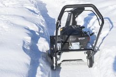 Snowblower at work on a winter day. Snowplow removing snow after blizzard. Clearing the ice. Snow removal machine. Clear driveway. With a snowblower. Snow Stock Images