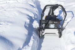 Snowblower at work on a winter day. Snowplow removing snow after blizzard. Clearing the ice. Snow removal machine. Clear driveway. With a snowblower. Snow Stock Image