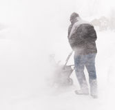 Snowblowing During Blizzard. Man snowblows out driveway during middle of blizzard conditions royalty free stock photography