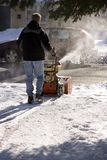 Snowblowing the Driveway. Man from behind snow blowing a driveway Royalty Free Stock Photography