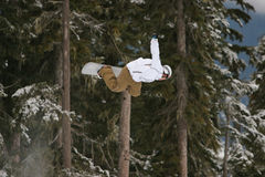 Snowboard B side Air. A snowboarder launches a trick high above the halfpipe Royalty Free Stock Image