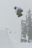 Snowboard B side Air. A snowboarder launches a trick high above the halfpipe Stock Images