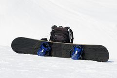Snowboard and backpack on ski slope. Snowboard and black backpack on ski slope in snow winter mountains at nice sun day Royalty Free Stock Photo