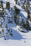 Snowboard Cliff Jump. A snowboard athlete drops off a large cliff into deep powder snow Stock Photos