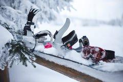 Snowboard com a asseguração coberta com a neve imagem de stock