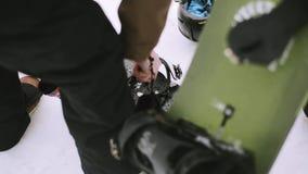 Snowboard de la fijación del Snowboarder por el destornillador en estación de esquí Manía extrema nevoso almacen de video