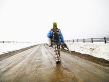 Snowboard de transport de femme. Photographie stock libre de droits
