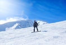 Snowboard del hombre joven en la montaña Imagen de archivo