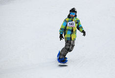 Snowboard del muchacho en cuesta del esquí Foto de archivo