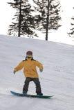 Snowboard del muchacho en una cuesta de montaña Imagen de archivo libre de regalías