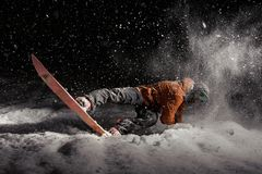 Snowboard dell'uomo alla notte sotto la neve immagini stock libere da diritti
