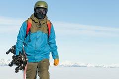 Snowboard della tenuta dello Snowboarder a disposizione e camminando alla cima di una montagna Fotografia Stock
