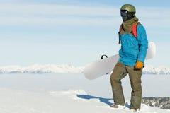 Snowboard della tenuta dello Snowboarder a disposizione e godendo del paesaggio alla cima della montagna Fotografie Stock Libere da Diritti