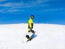 Snowboard della tenuta dello Snowboarder sopra la collina Immagine Stock Libera da Diritti