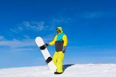 Snowboard della tenuta dello Snowboarder sopra la collina Fotografie Stock Libere da Diritti