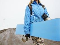 Snowboard di trasporto della donna. Fotografia Stock