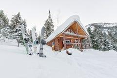Snowboard em chalés da casa na floresta do inverno com neve no mountai Fotos de Stock