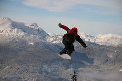 Snowboard flight. A snowboarder takes flight while jumping over a tree high on a mountain Royalty Free Stock Photos