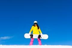 Snowboard för håll för Snowboarderflickaanseende, snö Fotografering för Bildbyråer