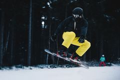 Snowboard Freestyle Jump. Snowboarder Jumping Through Air. With Dark Frozen Forest in Background Stock Image