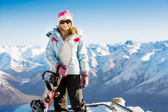 Snowboard girl. Woman holding snowboard with mountains in background stock photos